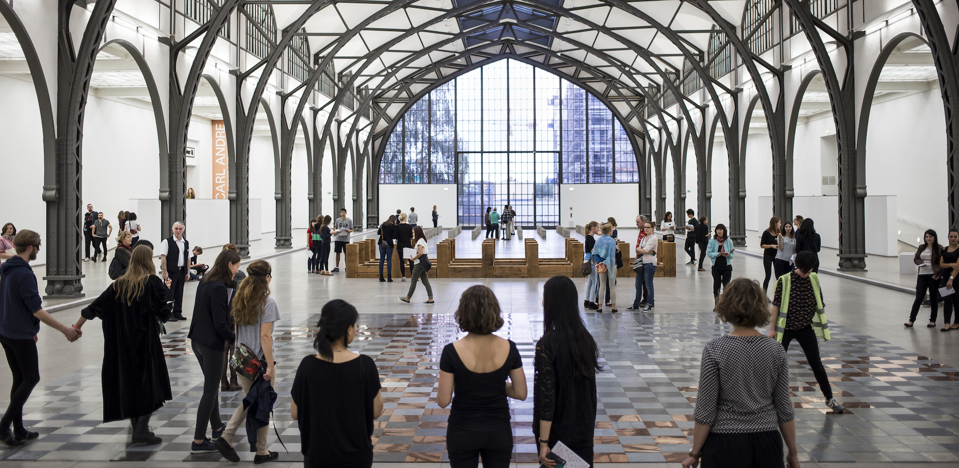 Students are in the main hall of the Hamburger Bahnhof – Museum für Gegenwart – Berlin in front of a work by Carl Andre.