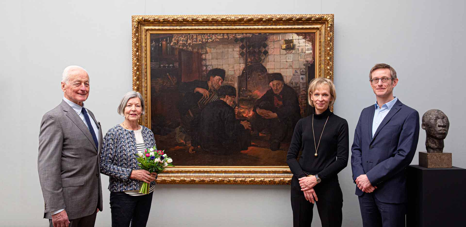 """Mr and Mrs Kaupomannsennecke, Christina Haak and Ralph Gleis in front of the painting """"Men by the Fireplace"""" by Paula Monjé in the Alte Nationalgalerie"""
