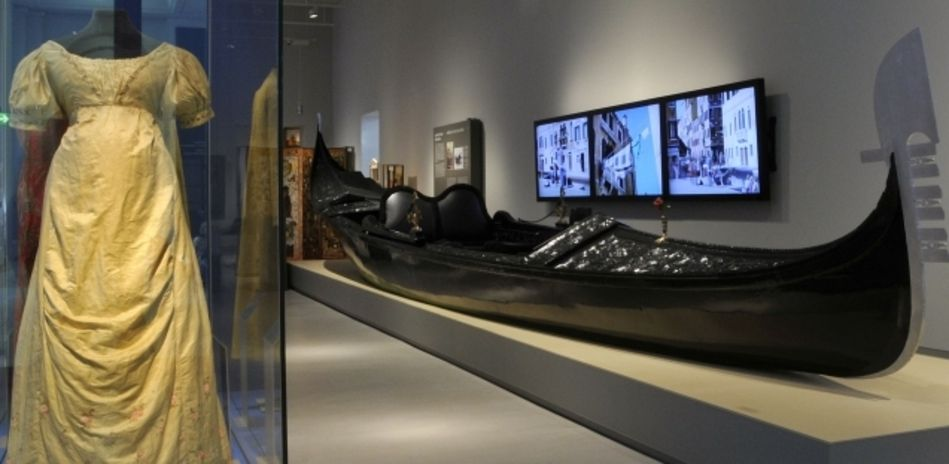 The image depicts an exhibition room. In the vitrine a dress is displayed, on the right side stands a venetian gondola.