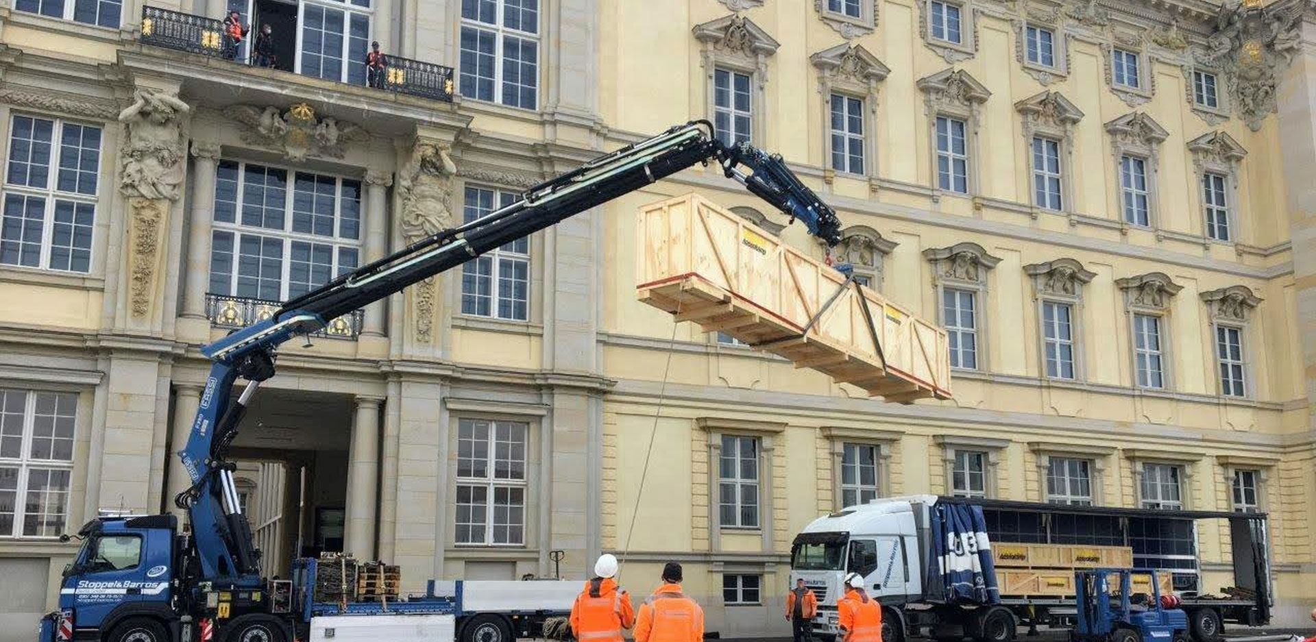 The totem pole being brought into the Humboldt Forum via a balcony.
